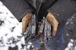A man holds a pair of coal