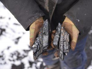 miner holding coal